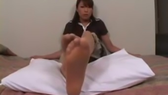 Japanese MILF with dark hair takes off her pantyhose and exposes feet