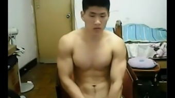 Beefy Chinese hunk takes off his clothes and jerks off his cock