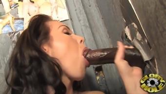 Maggie Matthews sucks on a monster black cock through a gloryhole