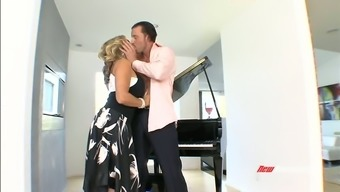 Stunning blond MILF Amber Lynn Bach gives solid BJ to cute brutal stud near piano