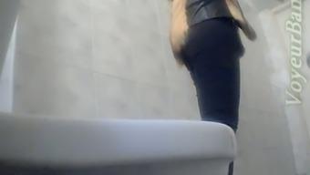 Slender white stranger girl in the toilet room shows her ass on voyeur cam