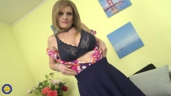 Mature blonde granny Raina W. plays with her saggy tits on the couch