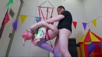 Submissive gal is tied up and hung above the floor before being fucked